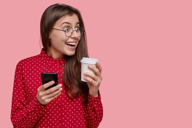 Joyeux étudiant aux longs cheveux noirs, remarque une scène drôle de côté, tient un téléphone portable moderne et une tasse de café jetable, porte des lunettes