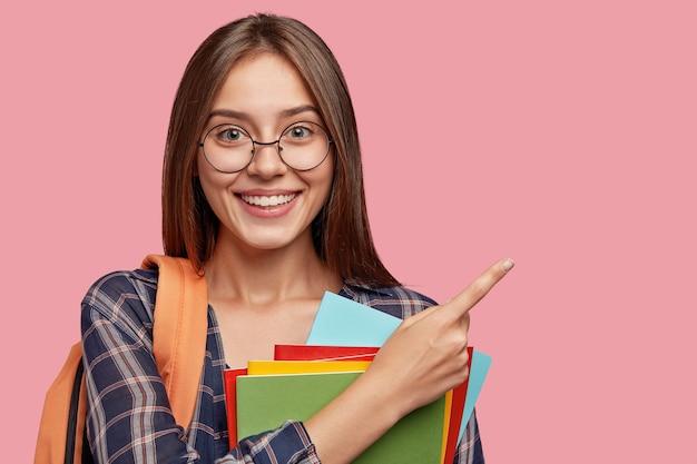 Joyeux étudiant posant contre le mur rose avec des lunettes
