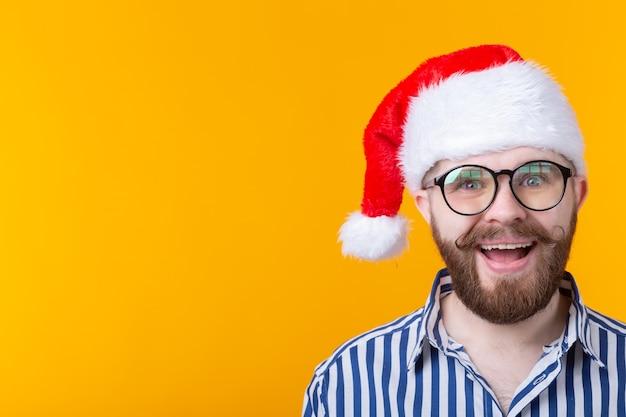 Joyeux fou mignon jeune hipster mâle en chapeau de père noël rouge posant sur le mur jaune. le concept de noël et du nouvel an.