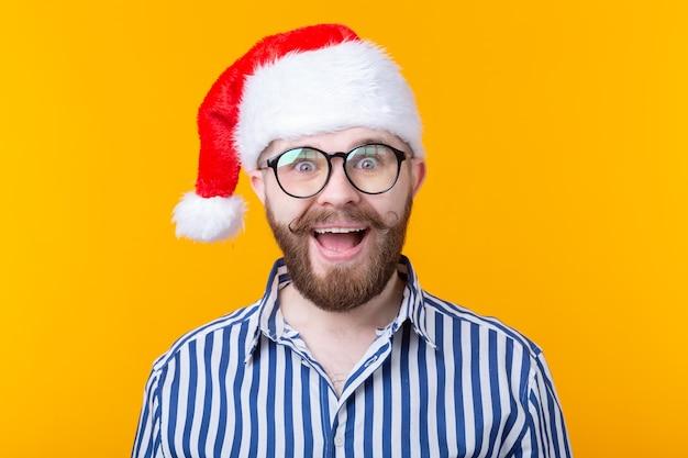 Joyeux fou mignon jeune hipster mâle en chapeau de père noël rouge posant sur le mur jaune. le concept de noël