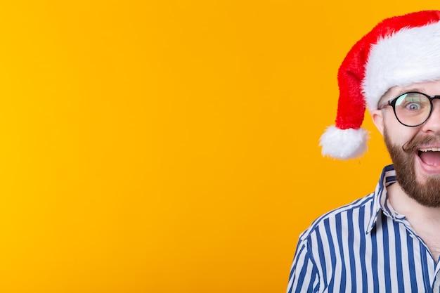 Joyeux fou mignon jeune hipster mâle en chapeau de père noël rouge posant sur le mur jaune. le concept de noël.