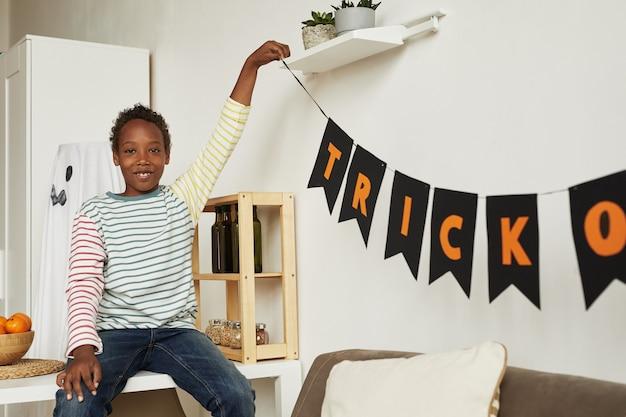 Joyeux garçon afro-américain portant des vêtements décontractés salle de décoration pour la fête d'halloween, espace copie