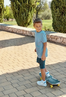 Joyeux garçon d'âge préscolaire en t-shirt apprenant à faire du skateboard dans un parc. maquette de chemise