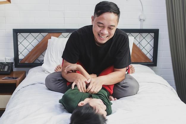 Joyeux garçon allongé sur le lit s'amusant et jouant avec son père