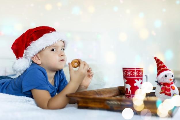 Joyeux garçon au lit mangeant des biscuits et buvant du cacao dans le chapeau du père noël bokeh sur fond noël