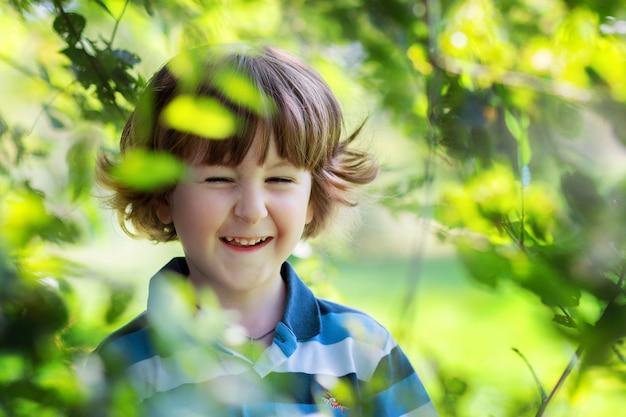Le joyeux garçon aux cheveux bouclés rit et se cache dans les branches des arbres