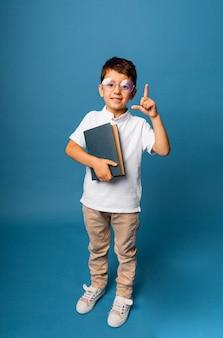 Joyeux garçon caucasien tenant un livre dans ses mains. garçon avec un livre pointe un doigt vers le haut sur un fond bleu.
