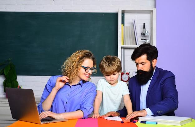 Joyeux garçon de famille des parents de l'école primaire encourageant leur petit fils avant le premier jour de