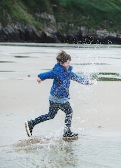 Joyeux garçon qui court sur la plage