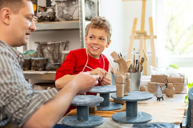 Joyeux garçon souriant tout en sculptant des animaux d'argile avec le professeur