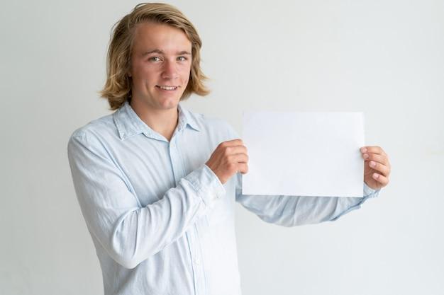 Joyeux gars blond présentant le nouveau produit