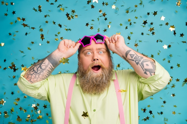 Joyeux gars en surpoids étonné sur fond bleu avec des confettis qui tombent