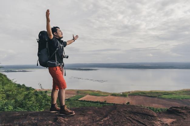 Joyeux geste de randonneur levant les bras au bord de la falaise, au sommet d'une montagne rocheuse