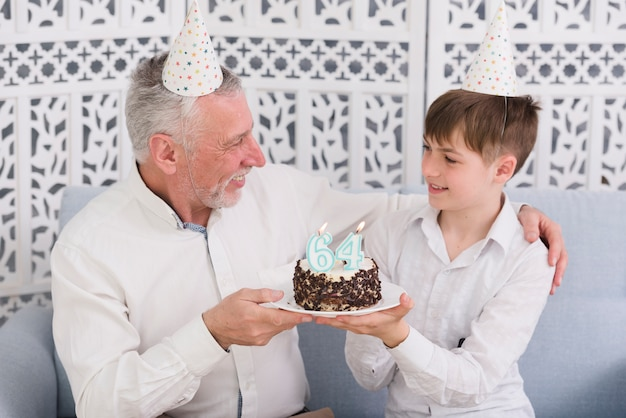 Joyeux grand-père et petit-fils se regardant tout en tenant un délicieux gâteau avec une bougie