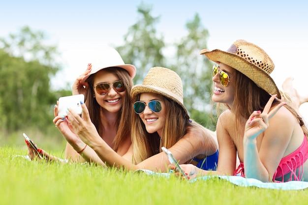 Joyeux groupe d'amis allongés sur l'herbe et prenant un selfie