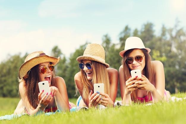 Joyeux groupe d'amis allongés sur l'herbe et textos
