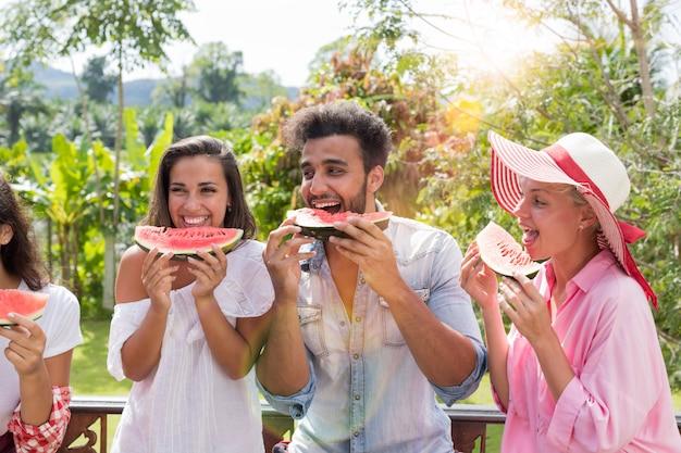 Joyeux groupe d'amis, manger de la pastèque ensemble à l'extérieur