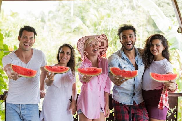 Joyeux groupe d'amis s'étirant tranche de pastèque