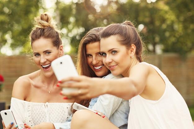 Joyeux groupe d'amis avec des smartphones assis à l'extérieur