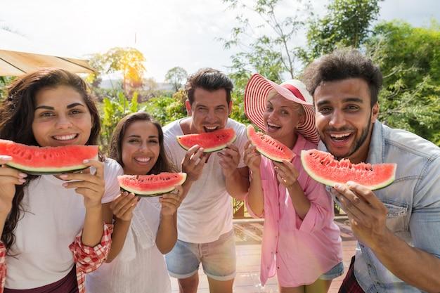 Joyeux groupe d'amis avec une tranche de pastèque sourire