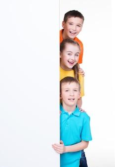 Joyeux groupe d'enfants derrière une bannière blanche - isolé sur fond blanc.