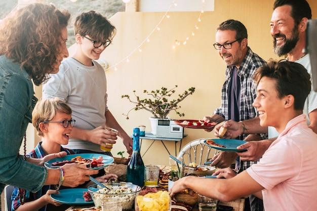 Joyeux groupe gai de personnes caucasiennes de génération et d'âge mélangés s'amusent ensemble en train de dîner ou de déjeuner ensemble