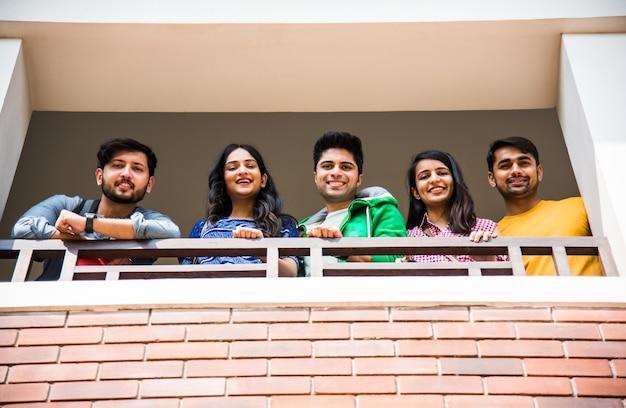 Joyeux groupe de jeunes asiatiques indiens d'étudiants ou d'amis riant ensemble assis, debout ou marchant sur le campus