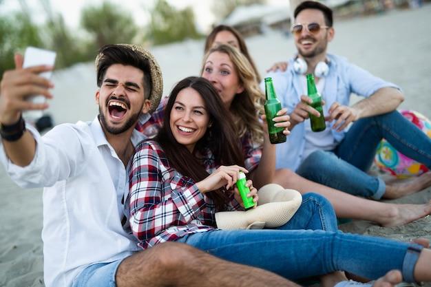 Joyeux groupe de jeunes s'amusant à la plage en été
