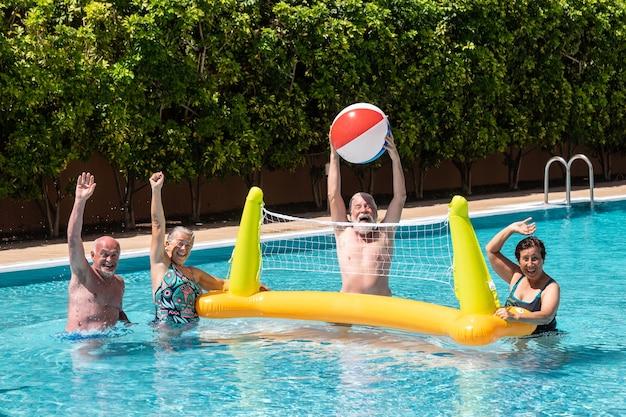 Joyeux groupe de personnes âgées jouant au volley-ball dans la piscine avec filet gonflable et ballon