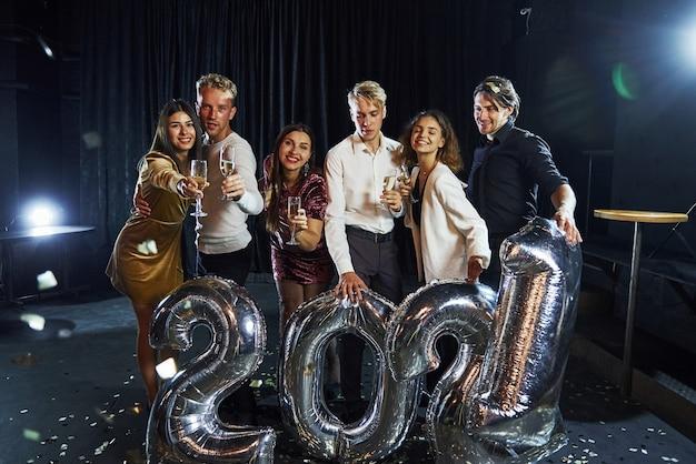 Joyeux groupe de personnes avec des boissons et des ballons à la main célébrant la nouvelle année 2021.