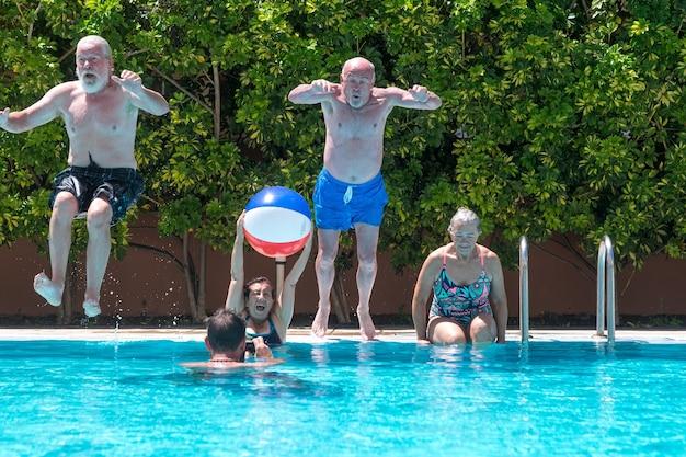 Joyeux groupe de personnes mûres profitant de l'été et de la piscine, sautant et jouant.
