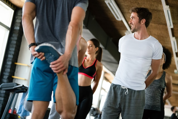 Joyeux groupe de sportifs dans une salle de sport. concepts sur le mode de vie et le sport dans un club de fitness