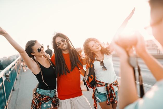 Joyeux groupe de touristes multiculturels posant sur le pont pendant que leur ami les prend en photo. concept de vacances d'été.
