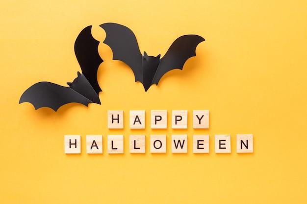 Joyeux halloween blocs de bois et chauves-souris en papier noir sur fond jaune. notion d'halloween. mise à plat, vue de dessus - image