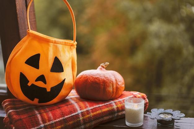 Joyeux halloween. citrouille et bougies sur un rebord de fenêtre confortable avec un plaid rouge. l'automne est douillet