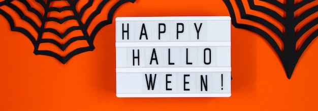 Joyeux halloween. décor de papier pour les vacances sur fond orange. format de bannière