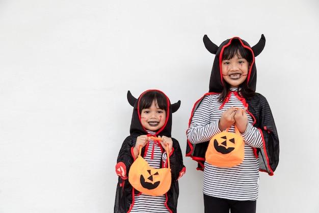 Joyeux halloween! deux enfants en costumes d'halloween et avec des citrouilles sur fond blanc