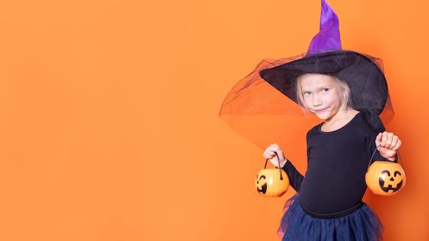 Joyeux halloween. les enfants fêtent halloween. fille joyeuse en costume de sorcière tenant un seau de bonbons en forme de lanterne citrouille sur fond orange. trick or treat concept.