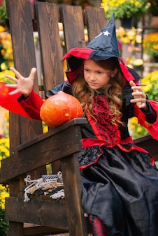 Joyeux halloween une fille en costume de sorcière avec une citrouille s'amusant à l'automne près de la maison