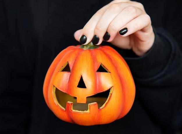 Joyeux halloween. mains féminines tenant des citrouilles drôles sur fond noir. manucure avec vernis à ongles noir