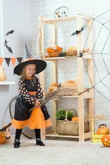 Joyeux halloween. une petite belle fille en costume de sorcière célèbre une maison dans un intérieur avec des citrouilles