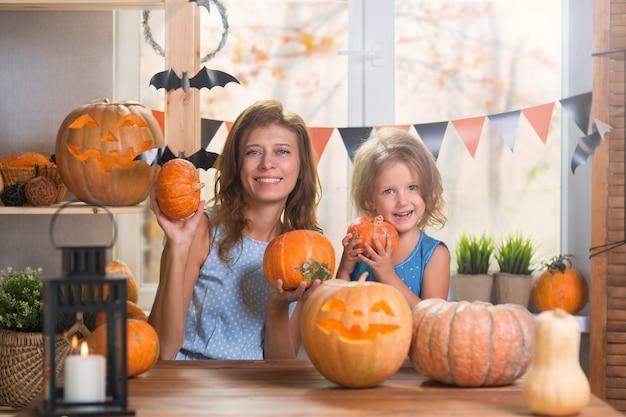 Joyeux halloween. petite belle fille de famille avec la mère célébrant la maison à l'intérieur avec des citrouilles