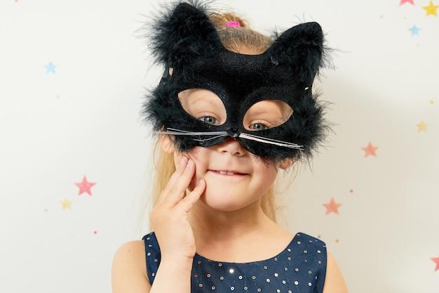 Joyeux halloween . petite fille enfant au masque de chat noir, costume de carnaval. drôle de tête