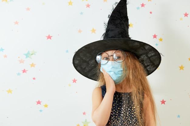 Joyeux halloween . petite fille enfant en costume de carnaval de sorcière et masque de protection du visage.