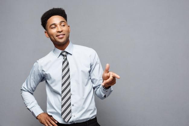Joyeux heureux jeune afro-américaine tenant le signe de pistolet avec les doigts pointant vers l'autre.