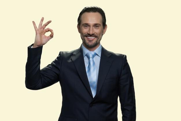 Joyeux homme d'affaires d'âge moyen montrant un geste correct. bon signe isolé sur fond jaune.