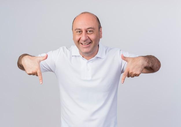 Joyeux homme d'affaires mature occasionnel pointant vers le bas isolé sur fond blanc