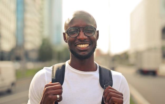Joyeux homme africain souriant avec des lunettes portant un t-shirt blanc et un sac à dos dans la rue