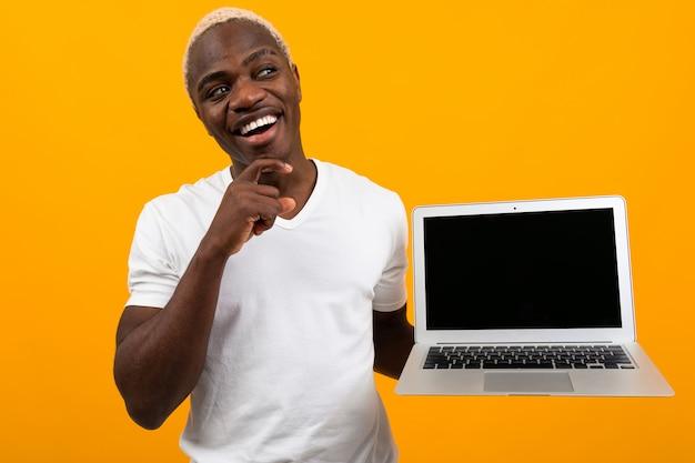 Joyeux homme africain souriant tenant un ordinateur portable avec une maquette sur jaune