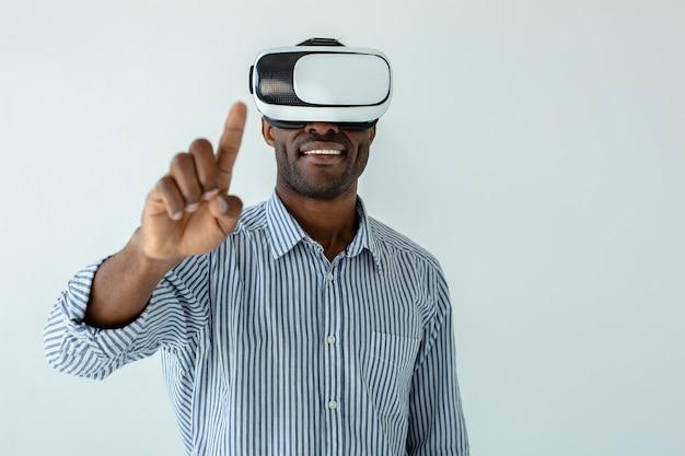 Joyeux homme afro-américain portant des lunettes vr tout en souriant